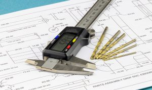Close up on an engineering vernier calliper and drill bits placed on engineering drawing background